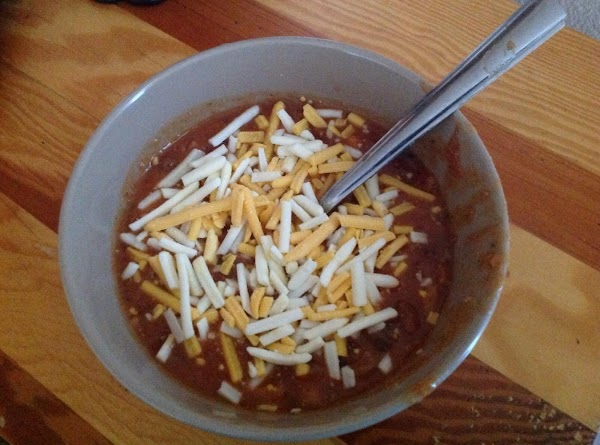 Add cans of tomatoes, and hot chili sauce to taste. Simmer until ready to...