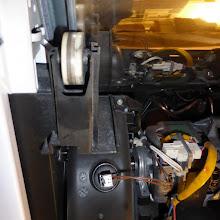 Photo: Trockner stehend, Ansicht von rechts. Spiegelblanke Trommel, links ein weißes Stützrad, darunter »Hamsterkäfig« des Ventilatorrades mit Temperaturfühler (?).