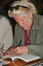 Photo: Stephen Roxborough signs a copy of the RASP poetry anthology.