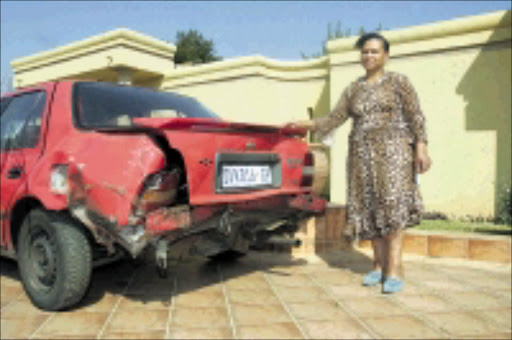 TAILGATED: Joan Mbele with her Nissan Sentra that was allegedly damaged when Ghanaian national Jonathan Quartey rammed into it. Pic. Veli Nhlapo. 03/08/08. © Sowetan.
