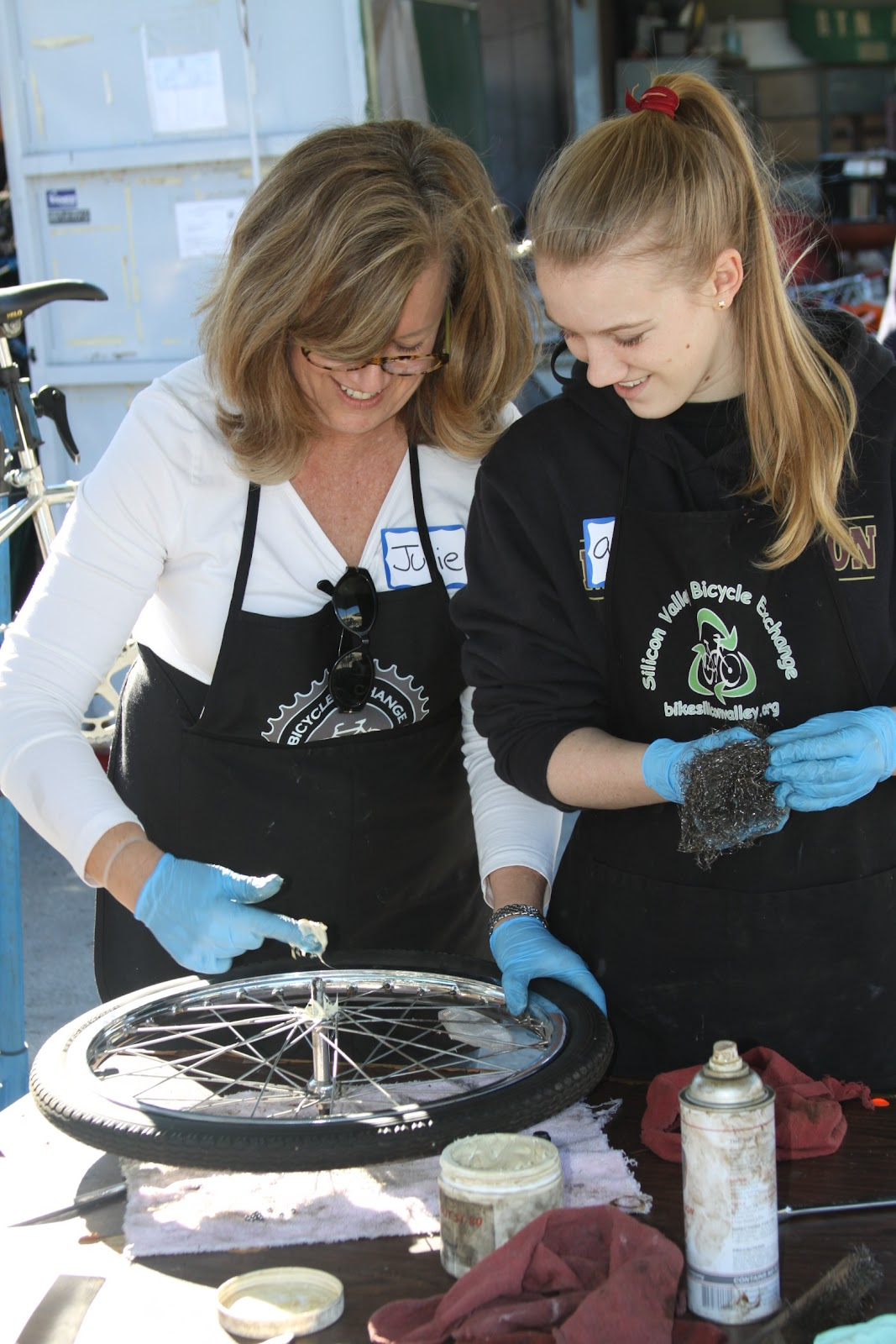 Julie greases the front hub of a donated bicycle, while Alaina cleans the bearings