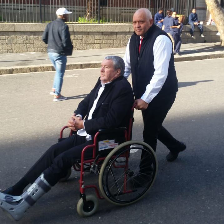 Gus Kouwenhoven' who is recovering from a broken leg' leaves Cape Town Magistrate's Court on June 25' 2018.