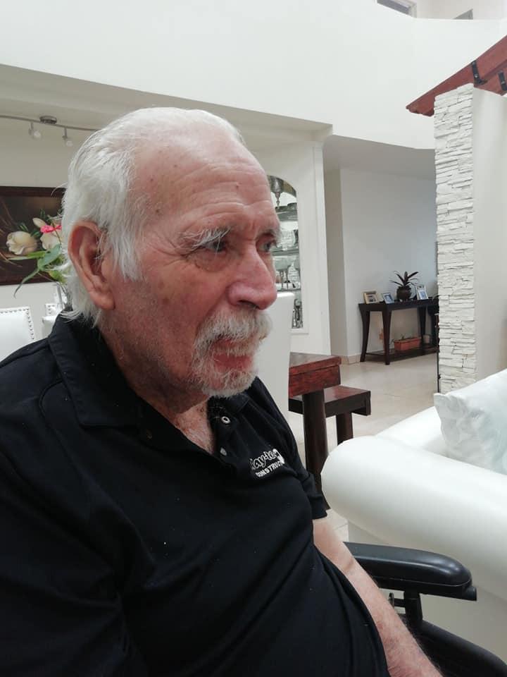 Un hombre mayor sentado en una silla  Descripción generada automáticamente con confianza media
