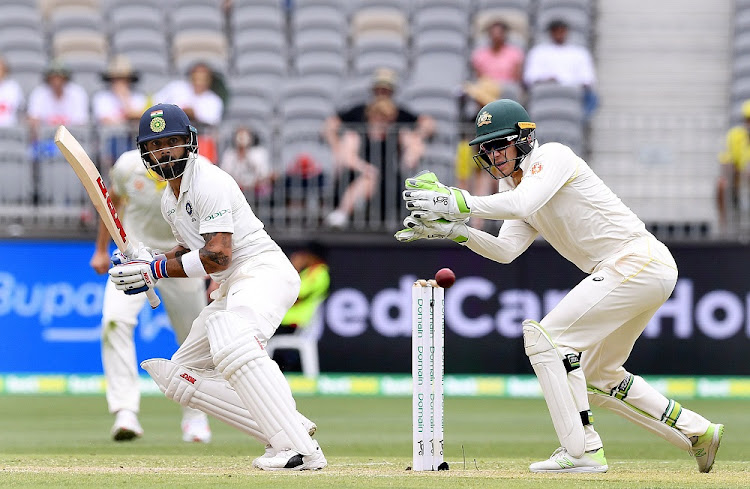 India's captain Virat Kohli plays a shot watched by Australia's captain and wicketkeeper Tim Paine at Perth Stadium in Perth, Australia, December 15 2018. Picture: AAP/DAVE HUNT/REUTERS