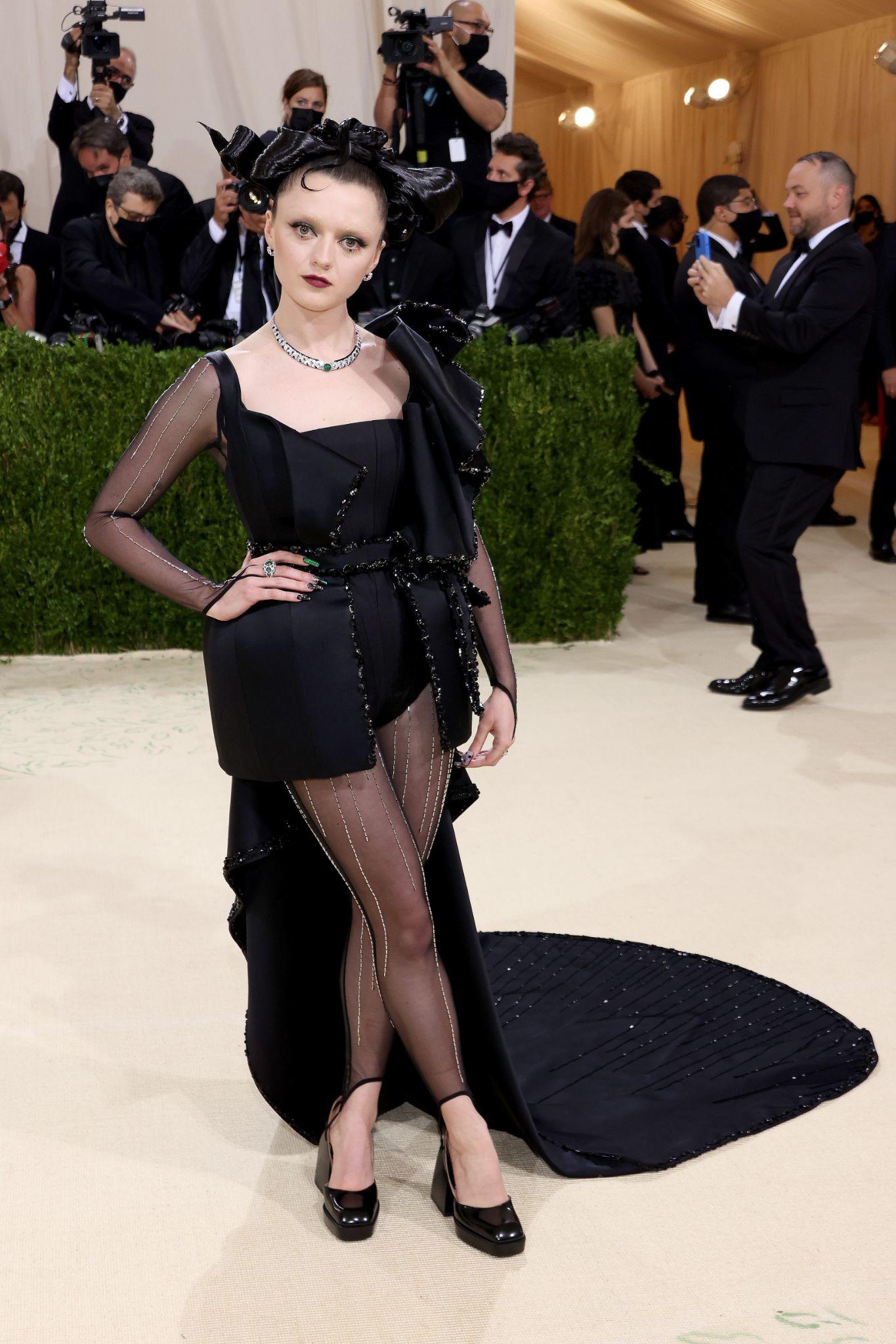 Mulher branca de cabelos pretos com acessório, usa vestido preto estruturado e curto que leva cauda que vai do ombro ao chão. Usa sapatos e meia calça preta. Foto: Getty Images. Post Looks icônicos do VMA e Met Gala 2021.