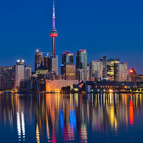 Red CN Tower by James Wheeler - City,  Street & Park  Skylines ( illuminated, nobody, polson street pier, skyline, harbor, metropolis, exterior, silhouette, toronto, architecture, travel, cityscape, city, center, sky, light, financial, highrise, structure, canada, twilight, lake, tourism, dusk, landmark, vacation, dawn, cn, canadian, scene, view, waterfront, reflection, spectacular, can, colorful, landscape, polson street peir, business, modern, skyscraper, cn tower, district, evening, downtown, tall, water, office, building, beautiful, ontario, scenic, urban, tower, blue, color, sunset, outdoor, night, high, scenery, glowing )