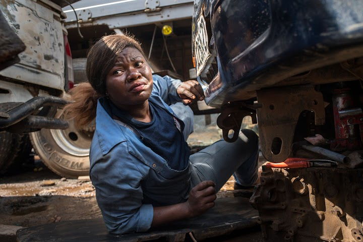 Princesse working underneath a car in blue work overalls.