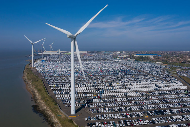 Imported automobiles sit at the docks in the shadow of wind turbines on April 23, 2020 in Sheerness, United Kingdom.