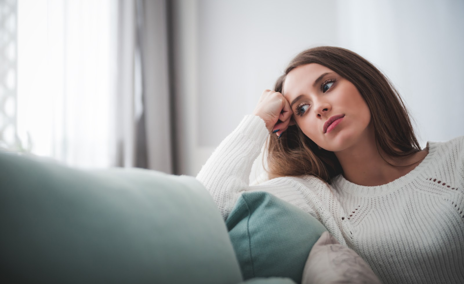 A woman sitting on the couch, deep in thought