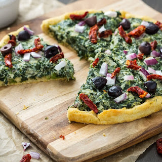 Pizza with Creamed Spinach, Sun-Dried Tomatoes, Red Onion, and Olives.