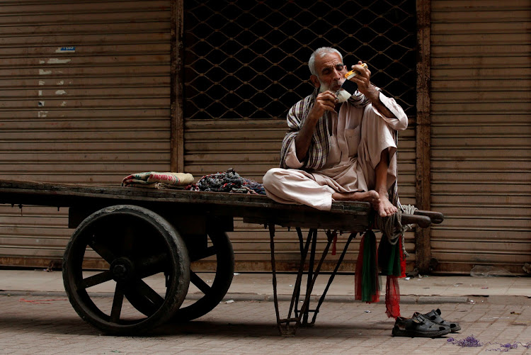 A labourer trims his moustaches while waiting for work on his push-cart along a wholesale market in Karachi, Pakistan.
