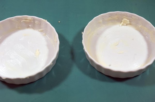 Divide the butter between the two ramekins, and thoroughly coat the bottom and sides.