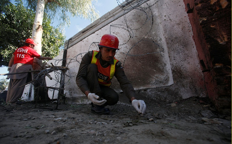 Volunteers collect remains at the site of a blast at the couthouse in Charsadda, Pakistan.   Picture: REUTERS