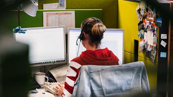 Frau mit Headset vor Bildschirmen