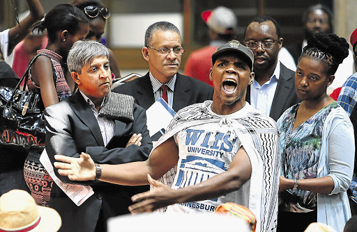 SA Students Congress president Mcebo Freedom Dlamini shouts out to fellow protesters at Wits University yesterday, while vice-chancellor Adam Habib, left, looks on. Sasco claimed the university was not registering students whose fees are to be paid by the National Student Financial Aid Scheme. Wits denied this. File photo