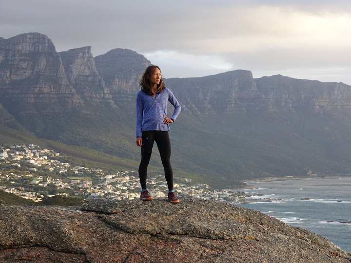 YiOu stands on a rock below Lions Head in front of the Twelve Apostles.