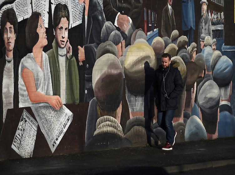 A man walks past a mural on the Falls Road a day after Northern Ireland's Deputy First Minister Martin McGuinness resigned, throwing the devolved joint administration into crisis, in Belfast, Northern Ireland, on Tuesday. Picture: REUTERS/CLODAGH KILCOYNE