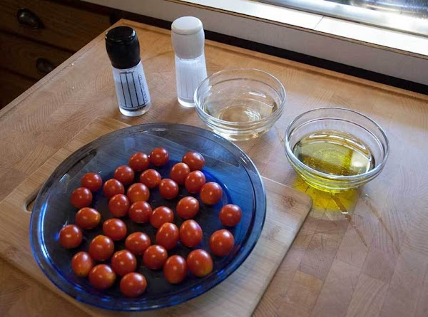 Rinse off the cherry tomatoes, and then place them into an ovenproof baking dish.