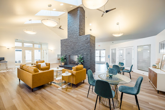 Emerald Gardens' upscale clubhouse seating area with fireplace and tables with chairs