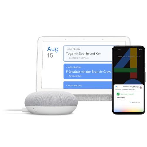 Ein Google Home, ein Laptop und ein Smartphone, auf denen Google Assistant zu sehen ist