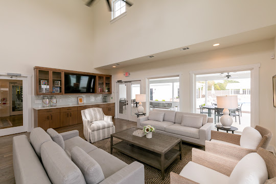 Community clubhouse seating area with plush couches and chairs, modern decor, and a TV