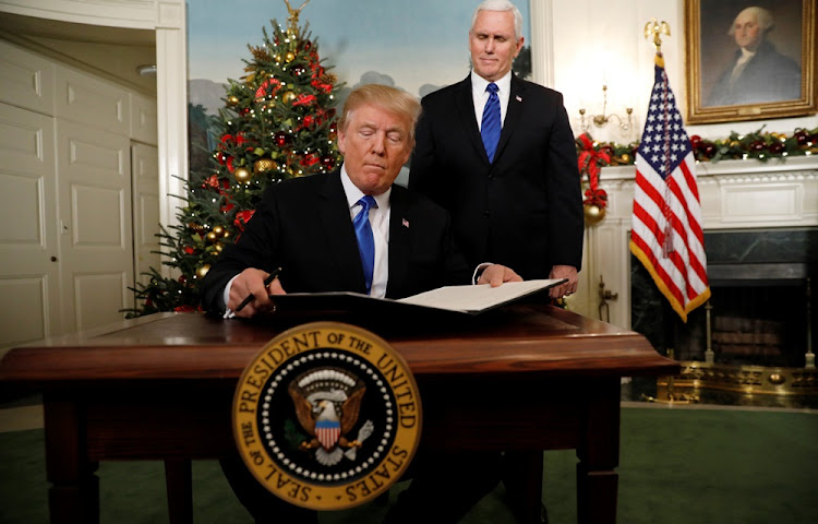 U.S. Vice President Mike Pence stands by as U.S. President Donald Trump signs a proclamation that states the United States recognizes Jerusalem as the capital of Israel and will move its embassy there, during an address from the White House in Washington, U.S., December 6, 2017.