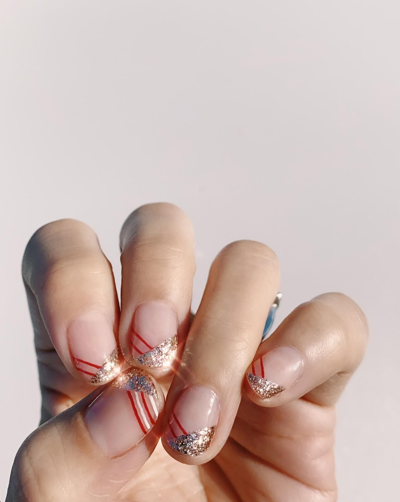 Clear nails with thick gold glitter on half of the tip & thin red & white stripes on the other half