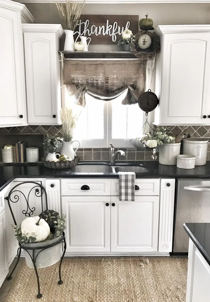 white farmhouse kitchen with fall decor above the kitchen cabinets. on top of the cabinets there are small pumpkins, a rustic sign, and vintage vases with foliage