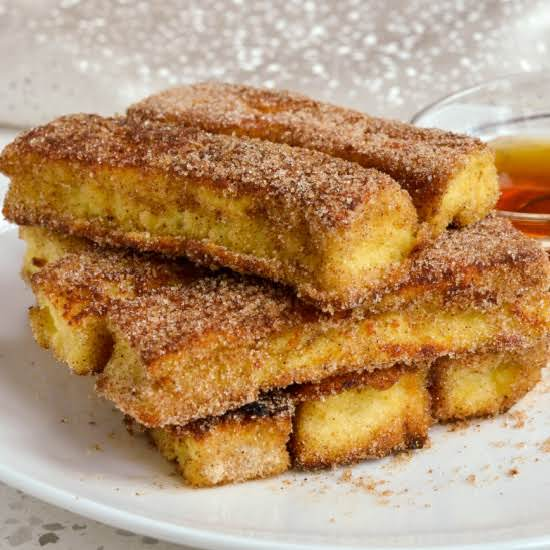 These Delectable French Toasts Sticks Are Pan Fried To Perfection And Rolled In Cinnamon Sugar.  They Come Together Quickly And Easily Using Many Ingredients That You May Already Have On Hand.