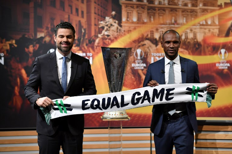 This photograph taken on April 13, 2018, shows former French soccer player and ambassador for the UEFA Europa League final in Lyon, Eric Abidal (R) posing with UEFA Managing Director of Communications Pedro Pinto and the UEFA Europa League Trophy ahead of the draw for the semi-finals round of the UEFA Europa League football tournament at the UEFA headquarters in Nyon.