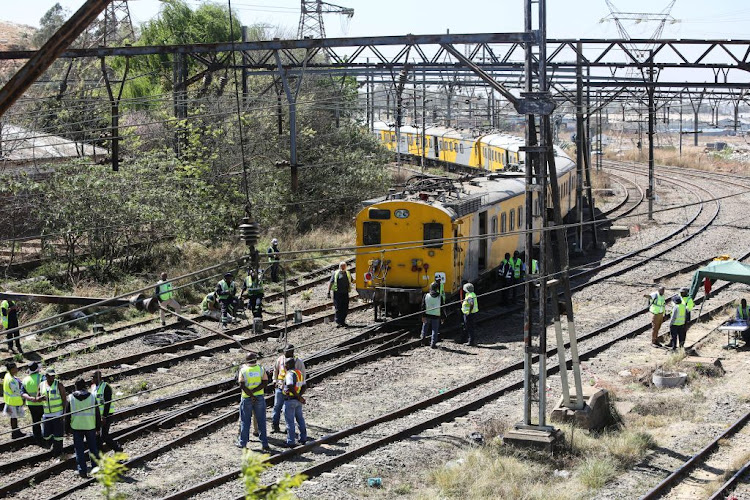 Metrorail workers are pictured on the scene where two trains collided on September 4, 2018, near the Booysens train station in Johannesburg. Over 100 commuters were injured in the incident.