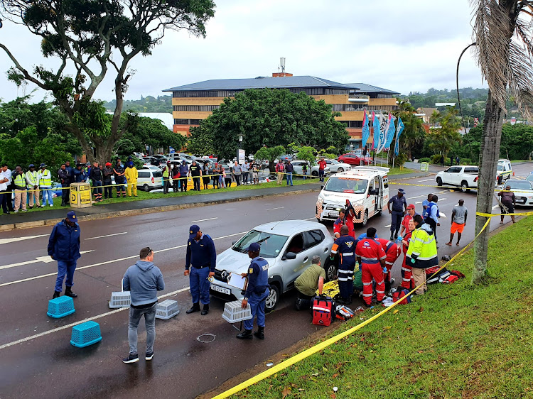 Paramedics treat a man who was shot multiple times outside a mall in Westville, Durban, on Friday.