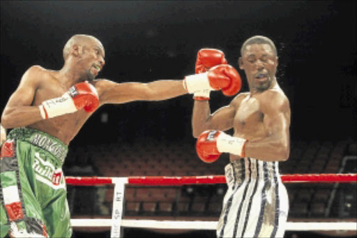 TAKE THAT: Takalani Ndlovu, right, takes   a punch from Jeffrey Mathebula during their IBF junior featherweight title fight at Carnival City in Ekurhuleni. Photo: Antonio Muchave