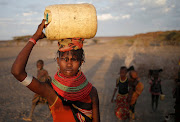 A woman carries a water canister in a village near Loiyangalani, Kenya.