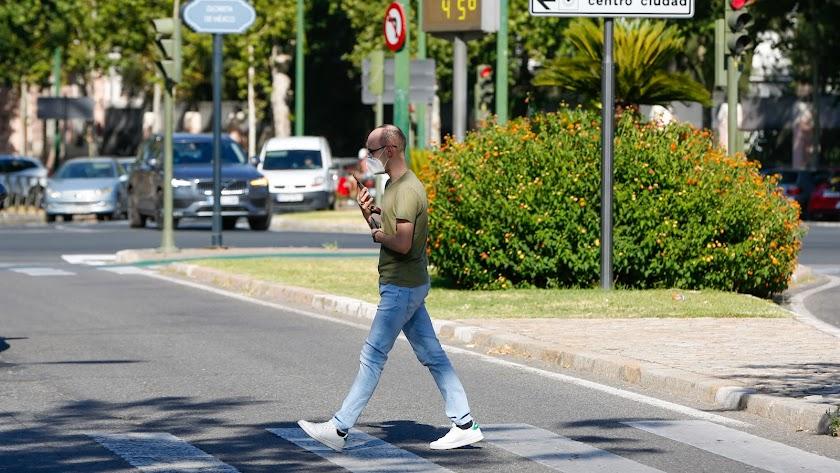 Un peatón paseando con mascarilla en la Avenida de la Palmera de Sevilla.