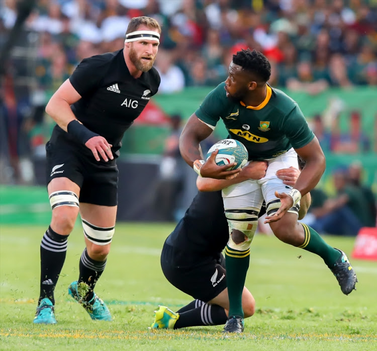 Springboks captain Siya Kolisi (R) pulls away from a tackle as his New Zealand counterpart charges in during the Rugby Championship match between South Africa and the All Blacks at Loftus Versfeld in Pretoria on October 06, 2018.