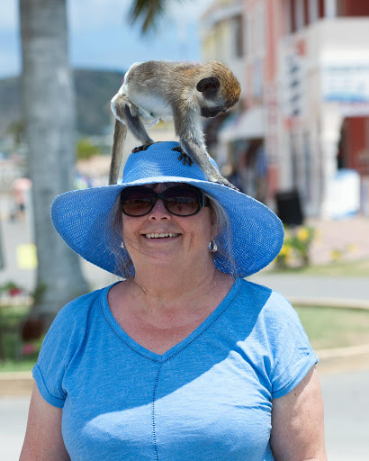 passenger-and-monkey-1.jpg - Watch out for locals who put green vervet monkeys on the heads of tourists for photo opps, as with this genial cruise visitor in St. Kitts.