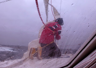 Photo: May 29th and there is a gale blowing. Stein struggling with hanking the storm genoa to the baby-stay before going hove-to (photo by Andrew Fraser).