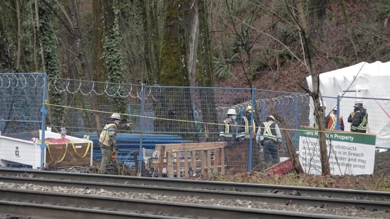 Trees behind razorwire with construction workers in camouflage trousers and yellow jackets and hats.  There is a sign about it being 'Trans Mountain property' and warning people not to obstruct.