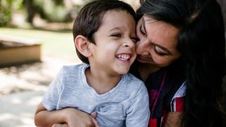 una mujer y un niño riéndose muy cerca