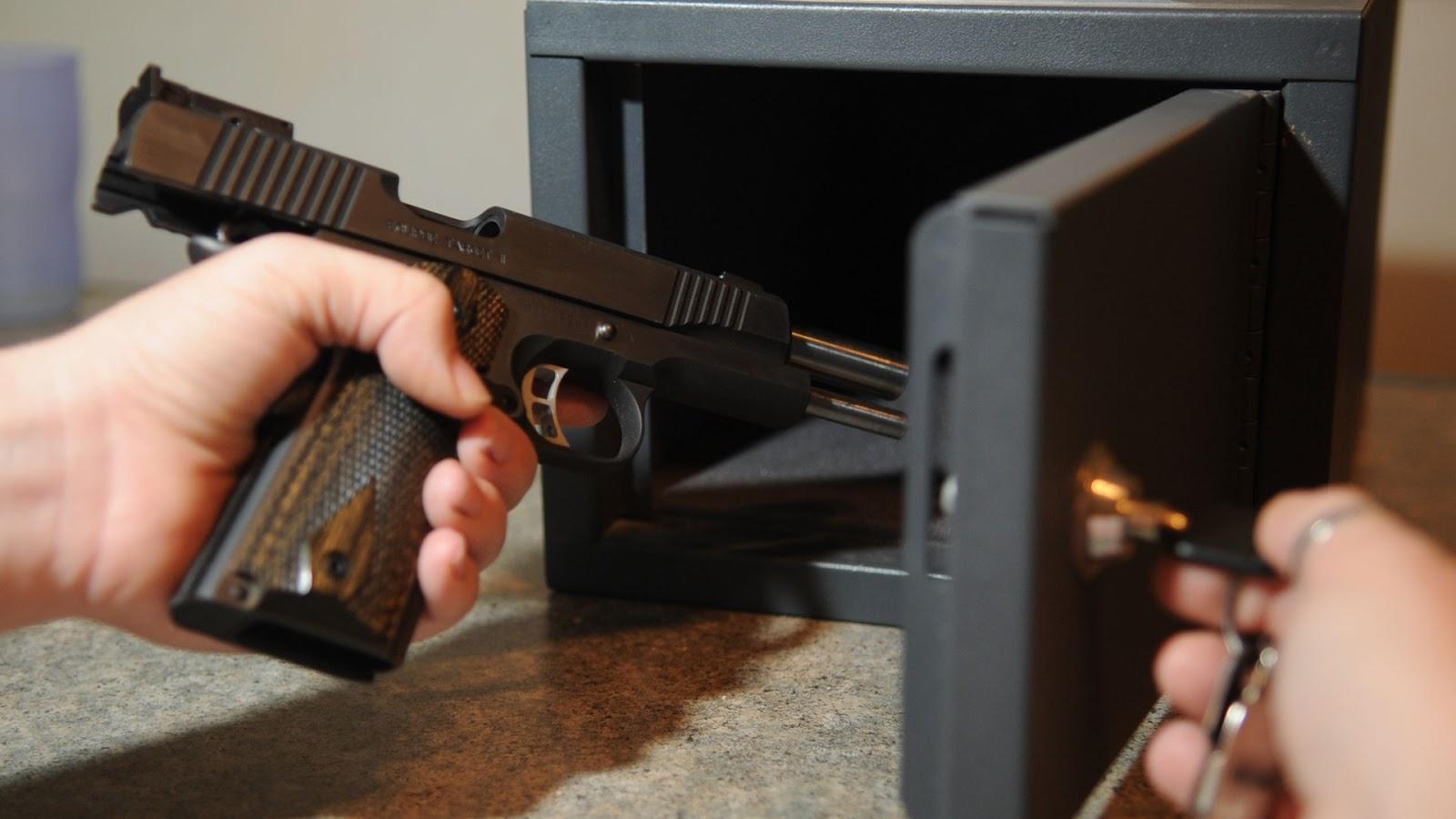 man locking pistol in safe