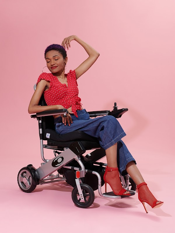 Model in a wheelchair with a red top and red boots in front of a pink background.
