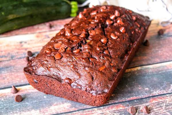 A Loaf Of Chocolatey Chocolate Zucchini Bread With Chocolate Chips On Top.