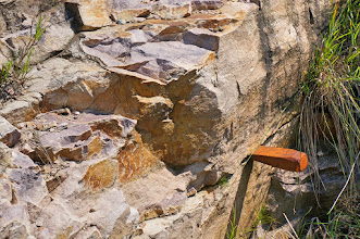 Photo: Wedges or chisels are placed into these cracks and then driven down with sledge hammers to break loose individual blocks of quartzite. Upon loosening a piece, it is worked free with a steel pry bar and allowed to drop to the floor of the quarry. Heavy sledge hammers are then used to break the bigger chunks of quartzite into smaller manageable pieces that can be lifted and thrown out the back of the quarry. The process of breaking out the quartzite is repeated many times until the pipestone layer is exposed.