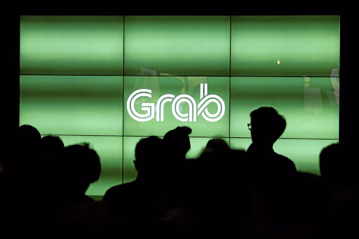 People wait for the start of ride-hailing company Grab's fifth anniversary news conference in Singapore in June 2017. Picture: REUTERS