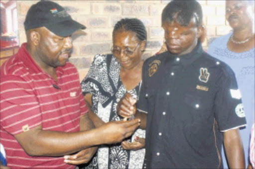 GIFT: Sipho Mokoena (red T-shirt) handing over the keys to the new house to Simphiwe Mkhonza. This was a few days before Christmas Day. Pic: Riot Hlatswayo. Circa Janaury 2010. © Sowetan.