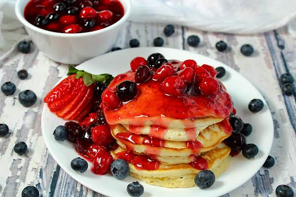 Pancakes With Fruit Topping Poured Over And Extra Fruit Topping On The Site.