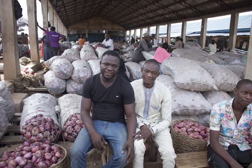 Onion merchants sit by their sack of onions