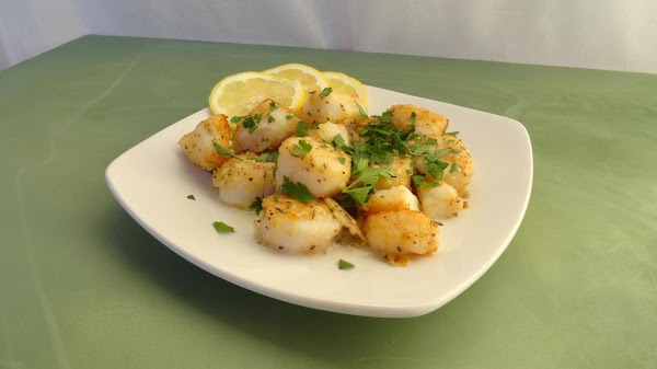 Sprinkle the scallops with the lemon juice and chopped parsley and serve.