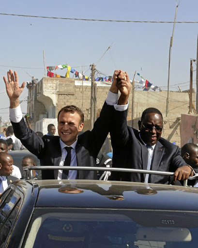 Priority: French President Emmanuel Macron, left, and Senegalese President Macky Sall wave in Saint-Louis, Senegal. Macron has emphasised the importance of building cultural exchanges in Africa. Picture: REUTERS